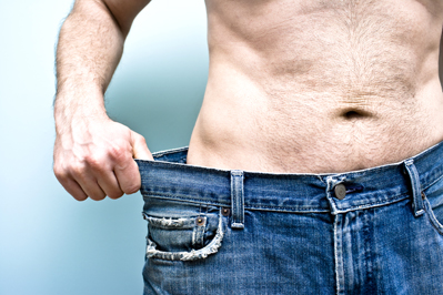 Man stands with an old pair of blue jeans indicating weight loss in his body